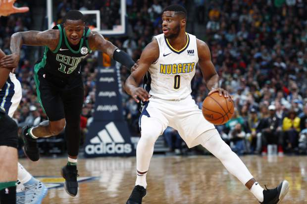 Boston Celtics guard Terry Rozier, left, fights past a pick to defend as Denver Nuggets guard Emmanuel Mudiay (0) drives to the basket in the first half of an NBA basketball game Monday, Jan. 29, 2018, in Denver. (AP Photo/David Zalubowski)