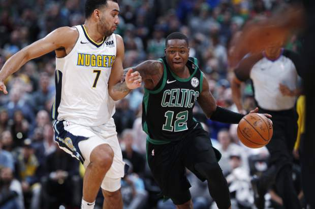 Boston Celtics guard Terry Rozier, right, fights past Denver Nuggets forward Trey Lyles to bring the ball up the court late in the second half of an NBA basketball game Monday, Jan. 29, 2018, in Denver. The Celtics won 111-110. (AP Photo/David Zalubowski)