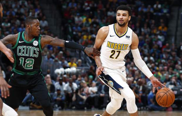 Boston Celtics guard Terry Rozier, left, reaches to slow down Denver Nuggets guard Jamal Murray who drives the lane in the first half of an NBA basketball game Monday, Jan. 29, 2018, in Denver. (AP Photo/David Zalubowski)