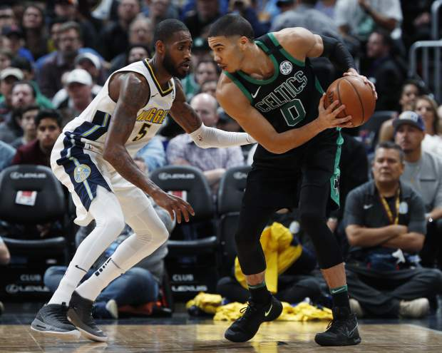 Denver Nuggets guard Will Barton, left, defends as Boston Celtics forward Jayson Tatum looks to drive to the basket in the first half of an NBA basketball game Monday, Jan. 29, 2018, in Denver. (AP Photo/David Zalubowski)