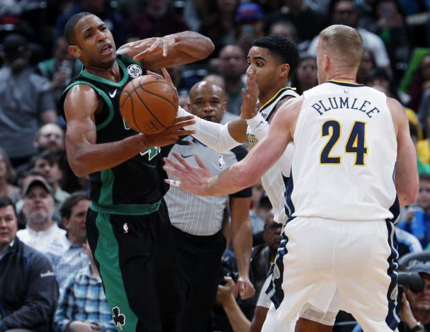 Boston Celtics forward Al Horford, left, loses control of the ball as Denver Nuggets guard Gary Harris, back right, and center Mason Plumlee defend in the first half of an NBA basketball game Monday, Jan. 29, 2018, in Denver. (AP Photo/David Zalubowski)