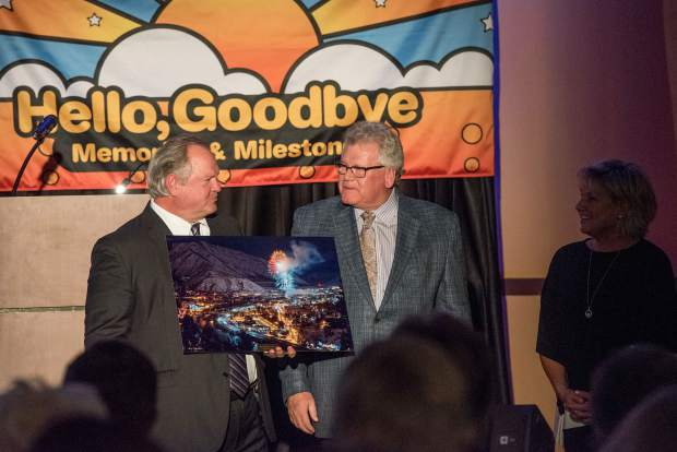 Glenwood Springs Chamber Resort Association Citizen of the Year Michael McCallum, left, is presented with a print of Steve Vanderleest's fireworks over Glenwood photo by Gregg Rippy, as McCallum's wife, Lee Ann, looks on.