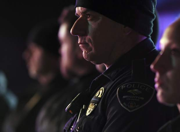 Brighton police officers wear a black ribbon over their badge for Adams County Sheriff's Deputy Heath Gumm in Brighton, Colo., Thursday, Jan. 25, 2018. Gumm was killed Wednesday night responding to a call in a residential area north of downtown Denver, the sheriff's office said. (John Leyba/The Denver Post via AP)