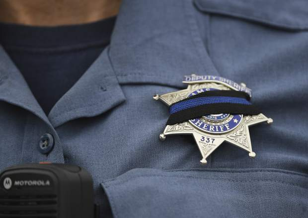 An Adams County Sheriff Deputy wears a black band across her badge after Sheriff's Deputy Heath Gumm was gunned down, Thursday, Jan. 25, 2018 in Thornton, Colo. Authorities in Colorado have arrested one man and are searching for two other suspects in connection with the killing of Gumm, a sheriff's deputy, leading some schools in the area to shut down. (RJ Sangosti/The Denver Post via AP)