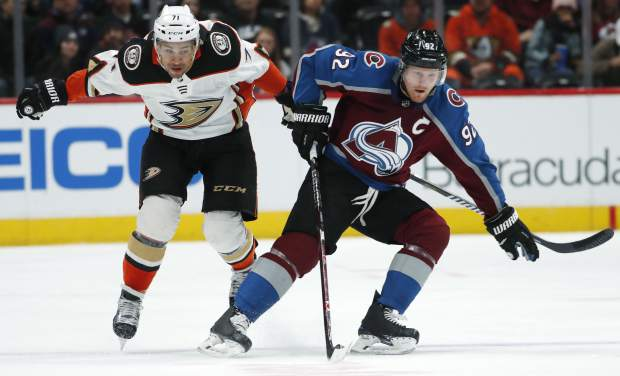 Colorado Avalanche left wing Gabriel Landeskog, right, of Sweden, picks up a loose puck in front of Anaheim Ducks right wing J.T. Brown in the first period of an NHL hockey game Monday, Jan. 15, 2018, in Denver. (AP Photo/David Zalubowski)