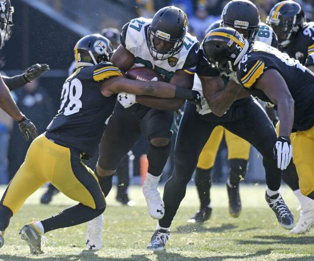 Jacksonville Jaguars running back Leonard Fournette (27) is tackled by Pittsburgh Steelers strong safety Sean Davis (28) during the first half of an NFL divisional football AFC playoff game in Pittsburgh, Sunday, Jan. 14, 2018. (AP Photo/Don Wright)