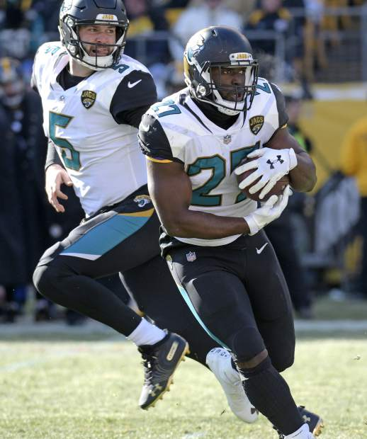 Jacksonville Jaguars quarterback Blake Bortles (5) hands off to Leonard Fournette (27) during the first half of an NFL divisional football AFC playoff game against the Pittsburgh Steelers in Pittsburgh, Sunday, Jan. 14, 2018. (AP Photo/Don Wright)