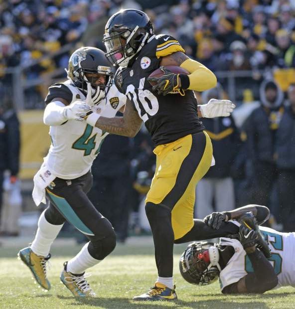 Pittsburgh Steelers running back Le'Veon Bell (26) is tackled by Jacksonville Jaguars free safety Tashaun Gipson, lower right, and Jacksonville Jaguars strong safety Barry Church, left, during the first half of an NFL divisional football AFC playoff game in Pittsburgh, Sunday, Jan. 14, 2018. (AP Photo/Don Wright)