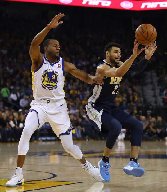 Denver Nuggets' Jamal Murray, right, passes away from Golden State Warriors' Andre Iguodala (9) during the first half of an NBA basketball game Monday, Jan. 8, 2018, in Oakland, Calif. (AP Photo/Ben Margot)