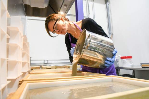 Osmia Organics founder Sarah Villafranco pours the mix of the Vetiver Grey into the molds at the facility in Carbondale.