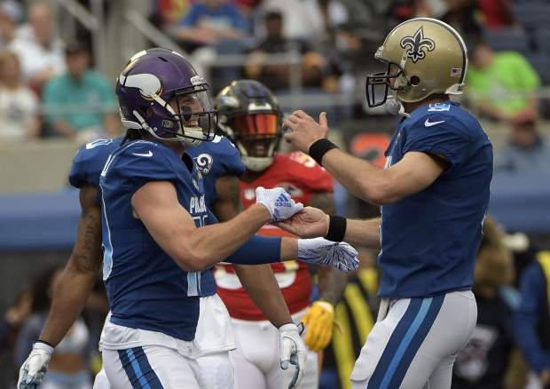 NFC quarterback Drew Brees (9), of the New Orleans Saints, celebrates after wide receiver Adam Thielen (19), of the Minnesota Vikings, scored a touchdown, during the first half of the NFL Pro Bowl football game, Sunday, Jan. 28, 2018, in Orlando, Fla. (AP Photo/Phelan M Ebenhack)