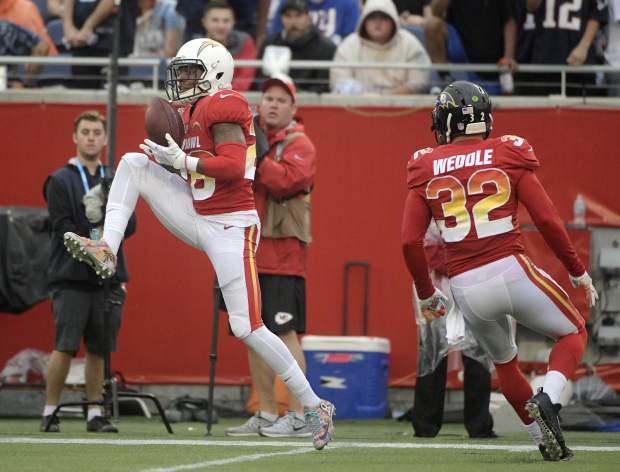 AFC cornerback Casey Hayward (26), of the Los Angeles Chargers, intercepts a pass, during the second half of the NFL Pro Bowl football game against the NFC, Sunday, Jan. 28, 2018, in Orlando, Fla. To the right is free safety Eric Weddle (32), of the Baltimore Ravens. (AP Photo/Phelan M Ebenhack)