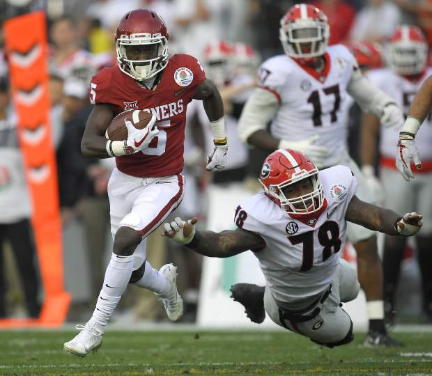 Oklahoma wide receiver Marquise Brown, left, runs the ball ahead of a tackle attempt by Georgia defensive tackle Trenton Thompson (78) during the first half of the Rose Bowl NCAA college football game Monday, Jan. 1, 2018, in Pasadena, Calif. (AP Photo/Mark J. Terrill)