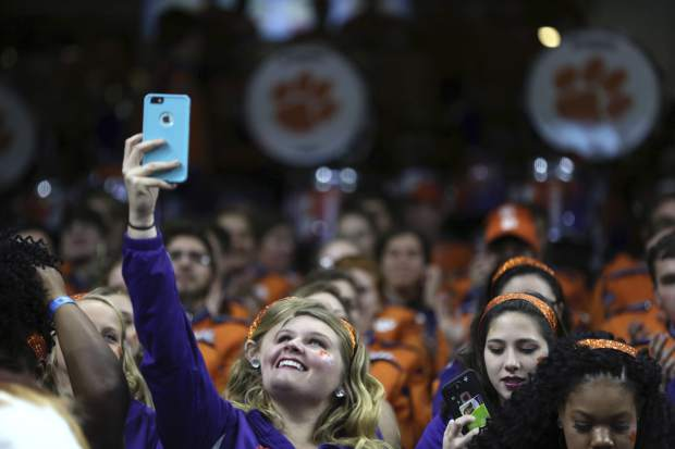 Ericka Pace, of the Clemson Tiger Band color guard, films their rehearsal inside the Superdome before the Sugar Bowl semi-final playoff game against the Alabama for the NCAA football national championship, in New Orleans, Monday, Jan. 1, 2018. (AP Photo/Rusty Costanza)
