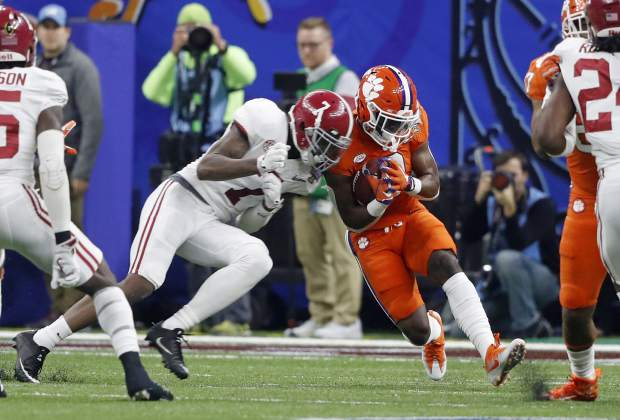 Clemson returner back Travis Etienne (9) is hit by Clemson defensive end Austin Bryant (7) on the opening kickoff in the first half of the Sugar Bowl semi-final playoff game for the NCAA college football national championship, in New Orleans, Monday, Jan. 1, 2018. (AP Photo/Gerald Herbert)