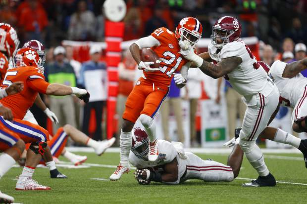 Alabama defensive lineman Raekwon Davis (99) tires to tackle Clemson wide receiver Ray-Ray McCloud (21) in the first half of the Sugar Bowl semi-final playoff game for the NCAA college football national championship, in New Orleans, Monday, Jan. 1, 2018. (AP Photo/Butch Dill)