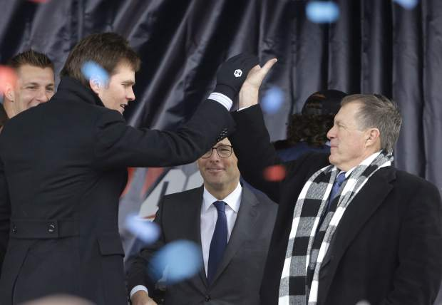 New England Patriots quarterback Tom Brady, front left, exchanges a high five with head coach Bill Belichick, right, during an NFL football Super Bowl send-off rally, Monday, Jan. 29, 2018, in Foxborough, Mass. The Patriots are to play the Philadelphia Eagles in Super Bowl 52, Sunday, Feb. 4, in Minneapolis. Patriots tight end Rob Gronkowski, left, and Jonathan Kraft, president of the Kraft Group, behind center, look on. (AP Photo/Steven Senne)