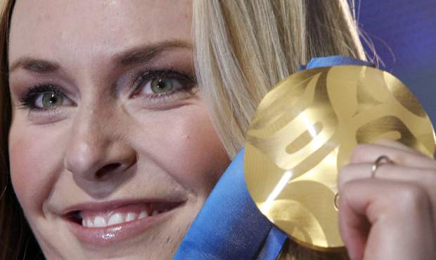 FILE - In this Feb. 17, 2010, file photo, Lindsey Vonn of the United States, shows the gold medal she won in the Women's downhill, during the medal ceremony at the Vancouver 2010 Olympics in Whistler, British Columbia. Vonn has some unfinished business on her agenda as she heads to the Pyeongchang Olympics. That includes trying to win more medals after missing the last Olympics because of a bad knee. (AP Photo/Luca Bruno, File)