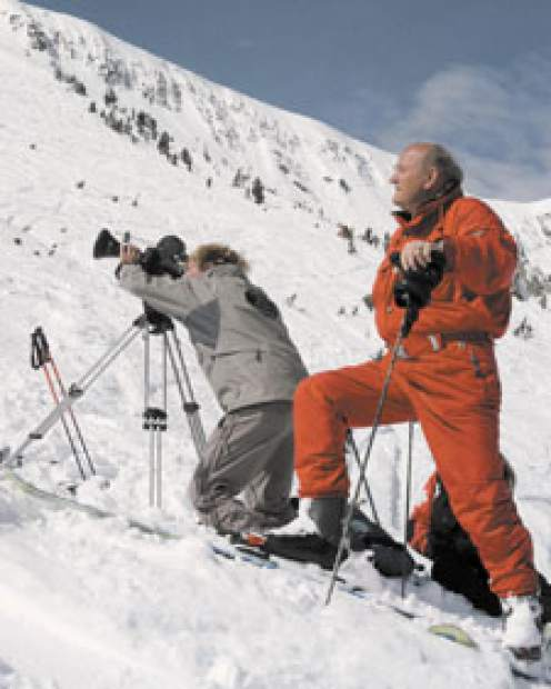 Warren Miller stands with cameraman Gary Nate as they film