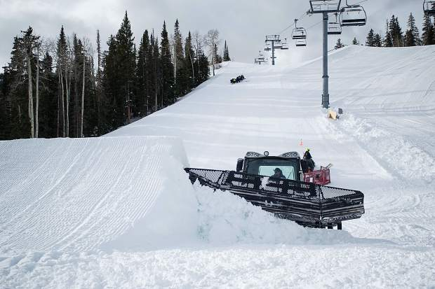 A snowcat driver clears off the shaved portions of snow on the side of the first jump on Saturday being set up for the U.S. Grand Prix event in Snowmass this week.