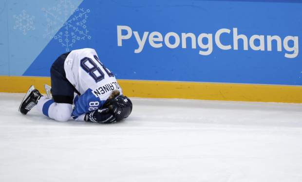 Ronja Savolainen, of Finland, grimaces in pain after colliding with Meghan Duggan, of the United States, during the first period of the semifinal round of the women's hockey game at the 2018 Winter Olympics in Gangneung, South Korea, Monday, Feb. 19, 2018. (AP Photo/Julio Cortez)