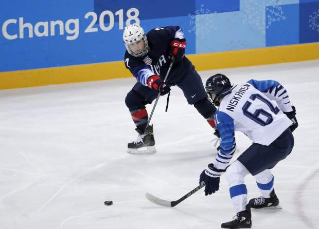 Monique Lamoureux-Morando (7), of the United States, passes the puck past Tanja Niskanen (61), of Finland, during the first period of the semifinal round of the women's hockey game at the 2018 Winter Olympics in Gangneung, South Korea, Monday, Feb. 19, 2018. (AP Photo/Julio Cortez)