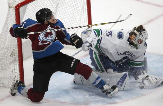 Vancouver Canucks goaltender Jacob Markstrom, right, stops a shot off the stick of Colorado Avalanche center Alexander Kerfoot in the third period of an NHL hockey game Monday, Feb. 26, 2018, in Denver. The Avalanche won 3-1. (AP Photo/David Zalubowski)