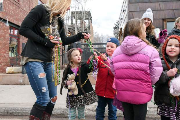 Kids collect as many beads as possible during Carbondale's Fat First Friday Parade down Main Street.