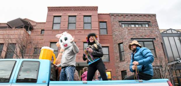 People in the Beer Works parade float throw out candy and beads to kids during the Fat First Friday parade down Main Street in Carbondale.