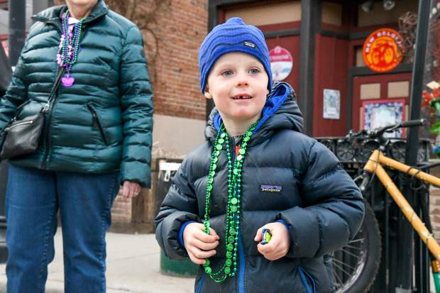 Five-year-old Tag Speaker collects as many beads as possible and watches the Fat First Friday Parade down Main Street in Carbondale.