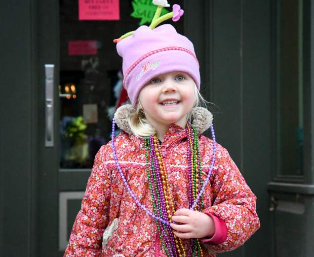 Three-year-old Molly Fain adds to her bead collection and watches the parade during Carbondale's Fat First Friday celebration on Main Street.