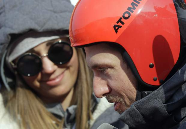Austria's Marcel Hirscher is interviewed in the mixed zone as his girlfriend Laura Moisl looks on after winning the gold medal in the men's giant slalom at the 2018 Winter Olympics in Pyeongchang, South Korea, Sunday, Feb. 18, 2018. (AP Photo/Michael Probst)