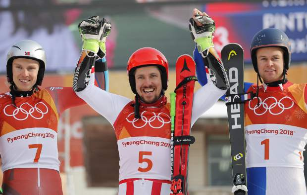 Norway's Henrik Kristoffersen, silver, Austria's Marcel Hirscher, gold, and France's Alexis Pinturault, bronze, from left, celebrate during the flower ceremony for the men's giant slalom at the 2018 Winter Olympics in Pyeongchang, South Korea, Sunday, Feb. 18, 2018. (AP Photo/Christophe Ena)