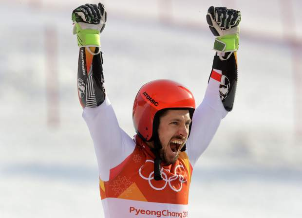 Austria's Marcel Hirscher who took the gold celebrates during the flower ceremony for the men's giant slalom at the 2018 Winter Olympics in Pyeongchang, South Korea, Sunday, Feb. 18, 2018. (AP Photo/Michael Probst)