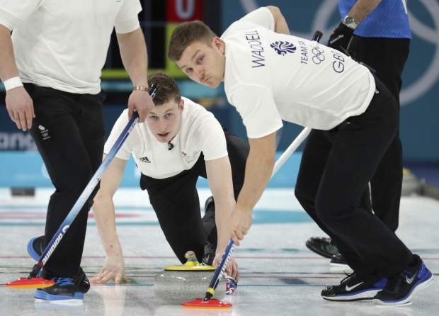 Britain's Thomas Muirhead, center, watches as teammates sweep ice during their men's curling match against Italy at the 2018 Winter Olympics in Gangneung, South Korea, Sunday, Feb. 18, 2018. (AP Photo/Aaron Favila)