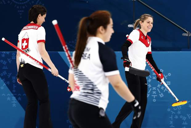 Switzerland's skip Silvana Tirinzoni, right, smiles after winning against Russian athletes at the women's curling match at the 2018 Winter Olympics in Gangneung, South Korea, Monday, Feb. 19, 2018. (AP Photo/Aaron Favila)