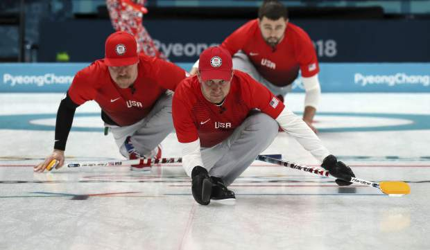 United States's skip John Shuster, center, slides on the ice with teammates before the start of the their men's curling match against United States at the 2018 Winter Olympics in Gangneung, South Korea, Sunday, Feb. 18, 2018. (AP Photo/Aaron Favila)