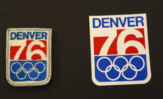 In this Feb. 1, 2018, photo, a patch and sticker used in Colorado's effort to secure an Olympic bid in 1976 are part of the memorabilia collection of the Denver Public Library in Denver. Over 40 years after becoming the first city to walk away from an Olympic bid, Denver is considering whether to try to again to host the Winter Games. (AP Photo/David Zalubowski)