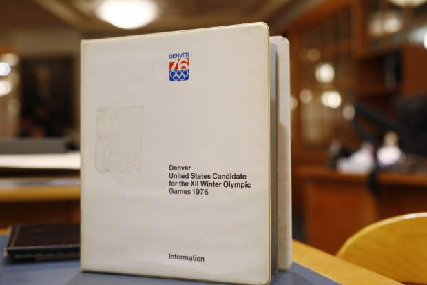 In this Feb. 1, 2018, photo, a binder filled with information used in Colorado's effort to secure an Olympic bid in 1976 is part of the memorabilia collection of the Denver Public Library in Denver. Over 40 years after becoming the first city to walk away from an Olympic bid, Denver is considering whether to try to again to host the Winter Games. (AP Photo/David Zalubowski)