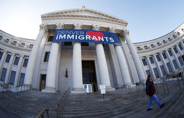 As viewed through a fisheye lens, a banner to welcome immigrants hangs over the main entrance to the Denver City/County Building Monday, Feb. 26, 2018, in Denver. The banner, which was put up the week of Valentine's Day, is both a way of letting immigrants know the city welcomes them and, with the fate of a program that protects hundreds of young immigrants from deportation up in the air, a message to Washington lawmakers to represent all of the city's residents. (AP Photo/David Zalubowski)