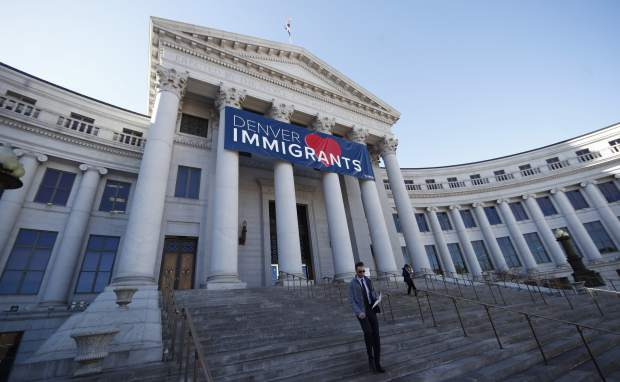 A banner to welcome immigrants hangs over the main entrance to the Denver City/County Building Monday, Feb. 26, 2018, in Denver. The banner, which was put up the week of Valentine's Day, is both a way of letting immigrants know the city welcomes them and, with the fate of a program that protects hundreds of young immigrants from deportation up in the air, a message to Washington lawmakers to represent all of the city's residents. (AP Photo/David Zalubowski)