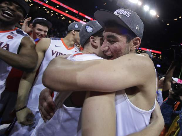 Virginia guard Ty Jerome, right, hugs guard Kyle Guy after Virginia defeated North Carolina 71-63 during an NCAA college basketball game for the Atlantic Coast Conference men's tournament title Saturday, March 10, 2018, in New York. (AP Photo/Julie Jacobson)