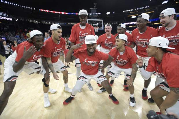 Cincinnati guard Trevor Moore, center, celebrates with teammates on the court after a win over Houston in an NCAA college basketball championship game at the American Athletic Conference tournament Sunday, March 11, 2018, in Orlando, Fla. (AP Photo/Phelan M. Ebenhack)