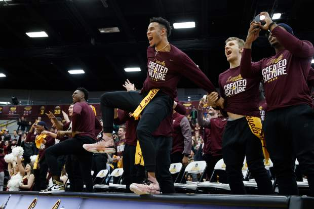 Loyola Ramblers guard Marques Townes, center, celebrates with other Loyola men's basketball players after the team was selected to play in the NCAA Tournament during a selection show watch party at Gentile Arena Sunday, March 11, 2018 in Chicago. (Armando L. Sanchez/Chicago Tribune via AP)