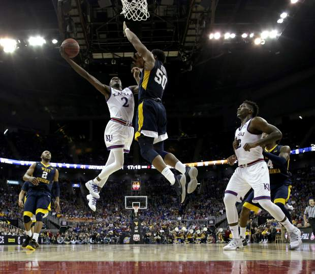 Kansas' Lagerald Vick (2) puts up a shot under pressure from West Virginia's Sagaba Konate (50) during the second half of the NCAA college basketball championship game in the Big 12 men's tournament Saturday, March 10, 2018, in Kansas City, Mo. Kansas won 81-70. (AP Photo/Charlie Riedel)