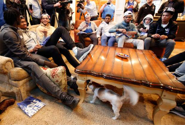 Coach John Calipari's dog Palmer, bottom center checks out members of the Kentucky basketball team as they watch the NCAA Tournament selection show at Calipari home, Sunday, March 11, 2018, in Lexington, Ky. (AP Photo/James Crisp)