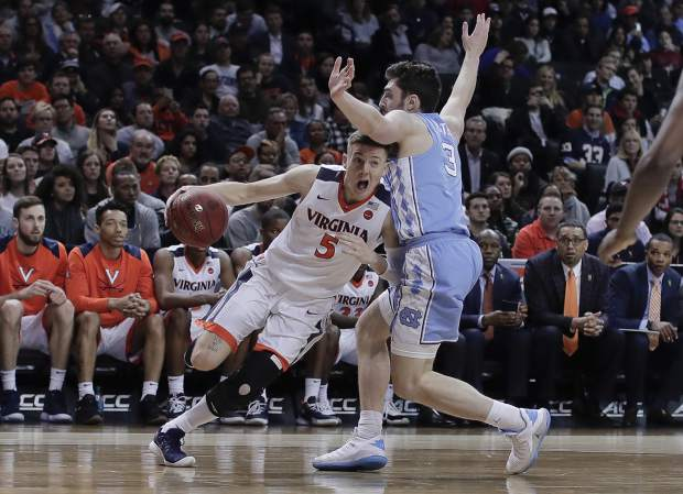 Virginia guard Kyle Guy drives against North Carolina guard Andrew Platek (3) during the second half of an NCAA college basketball game for the Atlantic Coast Conference men's tournament title Saturday, March 10, 2018, in New York. Virginia won 71-63. (AP Photo/Julie Jacobson)