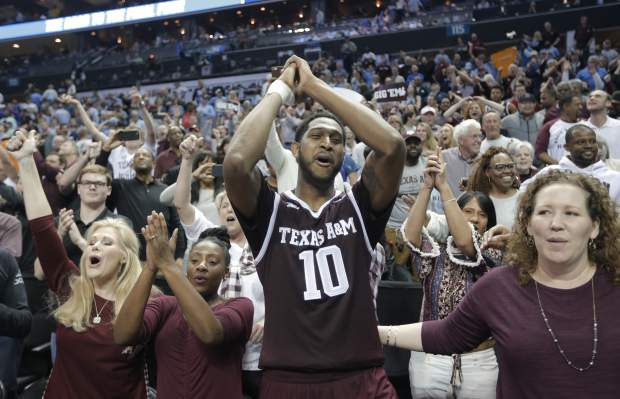 Texas A&M's Tonny Trocha-Morelos (10) celebrates with fans after a win over North Carolina in a second-round game in the NCAA men's college basketball tournament in Charlotte, N.C., Sunday, March 18, 2018. (AP Photo/Bob Leverone)