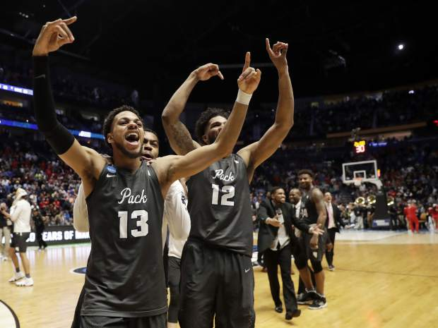 Nevada guard Hallice Cooke (13) and forward Elijah Foster (12) celebrate at the end end of the second half of a second-round game against Cincinnati, in the NCAA college basketball tournament in Nashville, Tenn., Sunday, March 18, 2018. Nevada defeated Cincinnati 75-73. (AP Photo/Mark Humphrey)