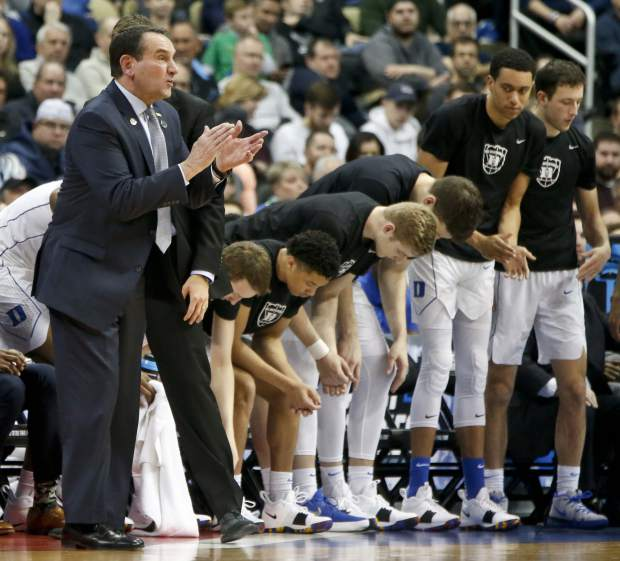 Duke head coach Mike Krzyzewski, left, claps beside his team as they play against Rhode Island during the first half of a second-round game in the NCAA men's college basketball tournament, Saturday, March 17, 2018, in Pittsburgh. (AP Photo/Keith Srakocic)